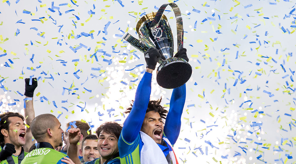 Roman Torres lifts the MLS Cup in victory as confetti falls from the sky in celebration of Seattle Sounders first MLS Cup win on December 10, 2016. Image by Dennis Marciniak of denMAR Media.