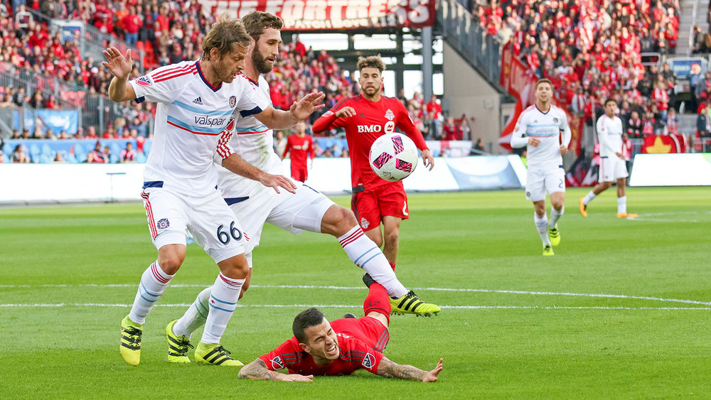 Sebastian Giovinco  taken to ground while two Chicago Fire defenders linger over him trying to get a touch on the ball. Image by Dennis Marciniak.