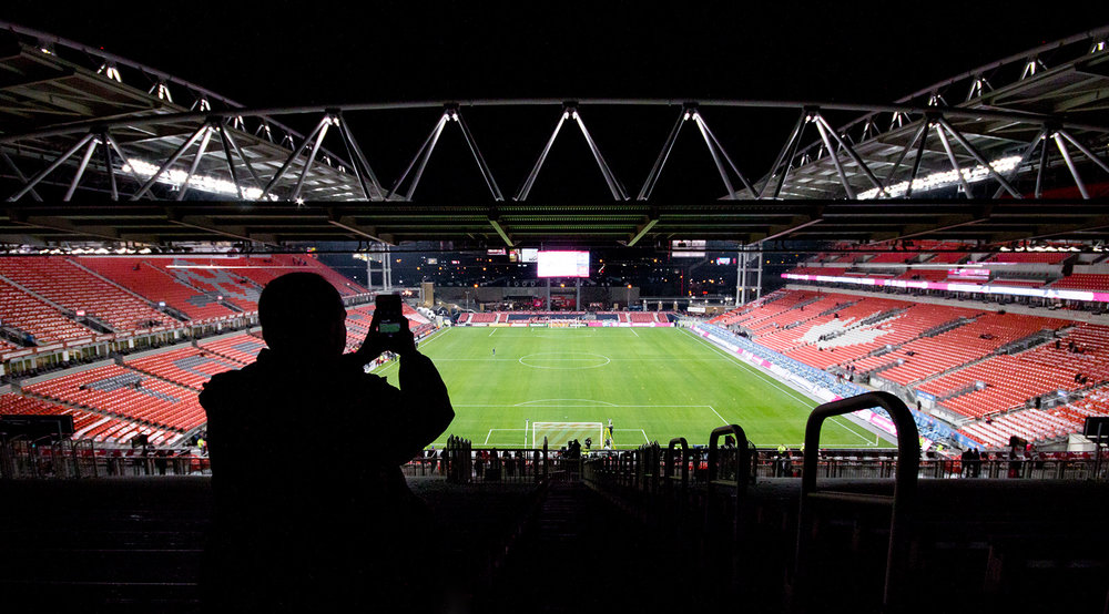 A fan taking a picture of view at BMO Field from the temporary stands during the 2016 MLS Cup Playoffs. Image by denMAR Media.
