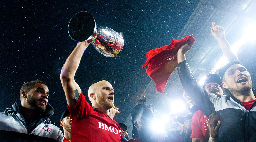Michael Bradley lifts the Eastern Conference Cup in 2016 in front of Toronto FC South End Supporters. Image by Dennis Marciniak of denMAR Media.