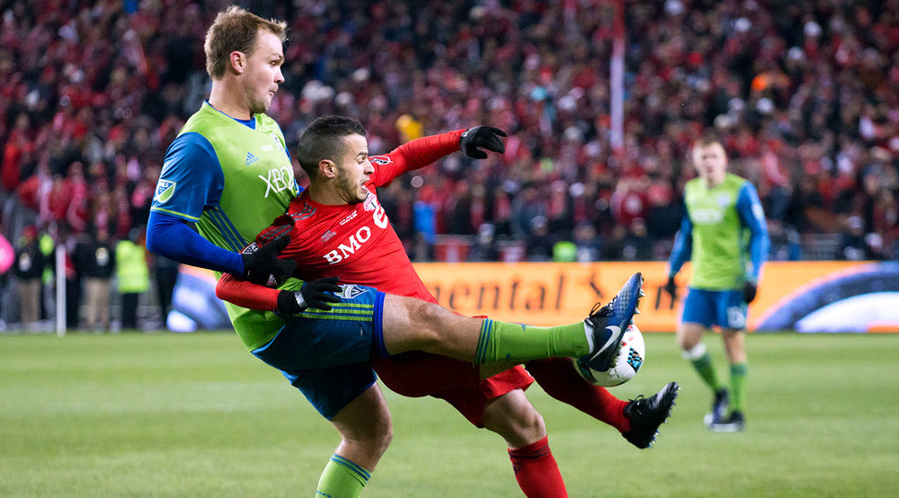Sebastian Giovinco and a Seattle Sounder defender interlocked and both going for the ball during the 2016 MLS Cup Final at BMO Field. Image by Dennis Marciniak of denMAR Media.