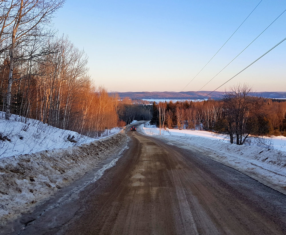 A truck driving down a rural winter road up in Barry's Bay, Ontario. Image by Dennis Marciniak of denMAR Media.