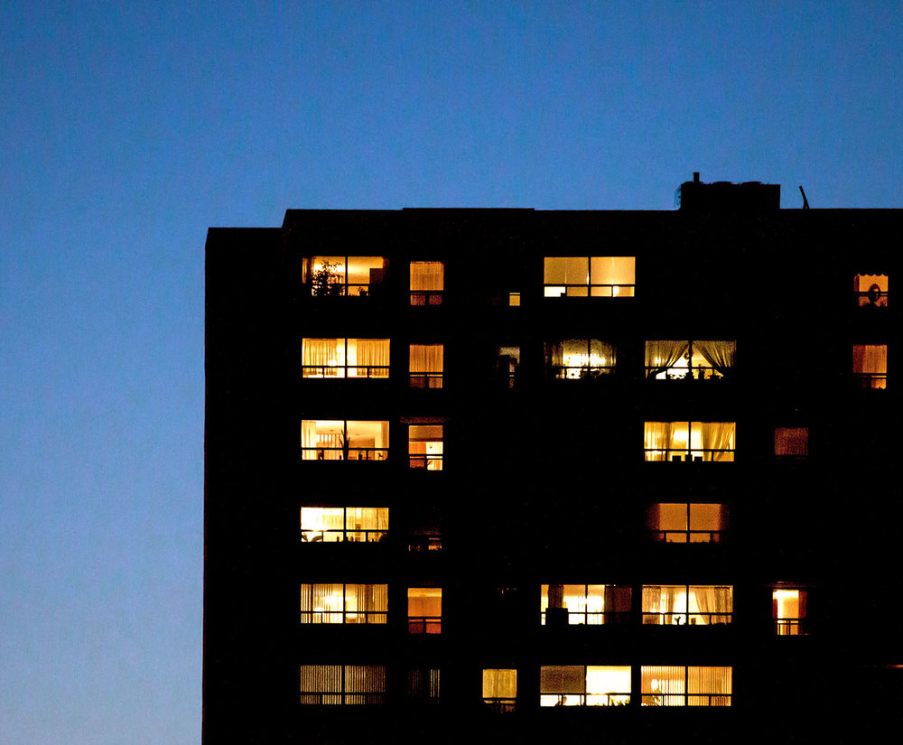 A residential building at night during magic hour in Toronto during the winter. Image by Dennis Marciniak of denMAR Media.