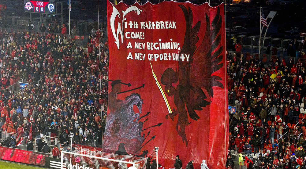 With Heartbreak Comes A New Beginning A New Opportunity banner in the South End Supporter's Section at BMO Field on March 31, 2017. Image by Dennis Marciniak of denMAR Media.