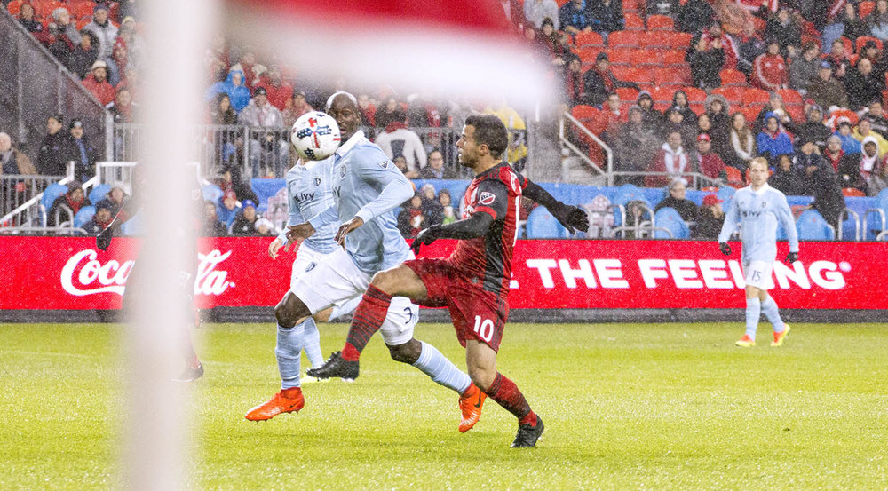 Sebastian Giovinco attempting to gain possession of the ball by a Sporting Kansas City defender with the corner kick flag in the foreground. Image by Dennis Marciniak of denMAR Media.