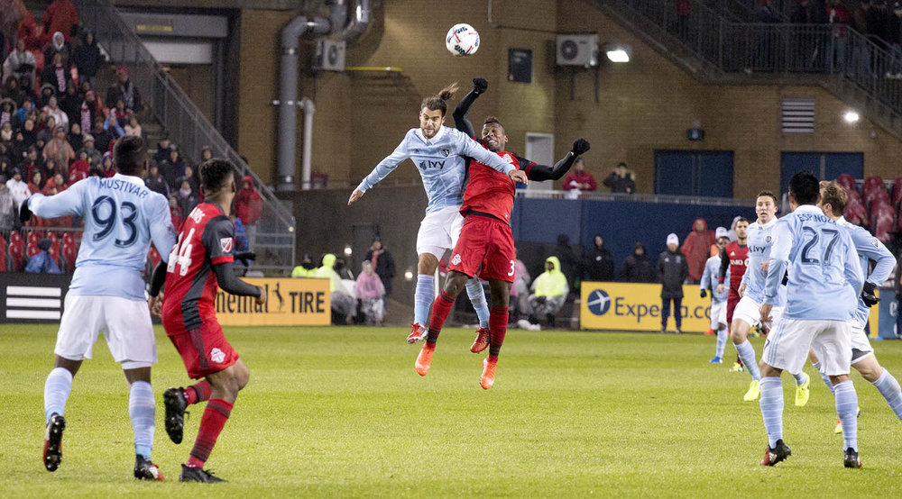 Armando Cooper goes into the air for a header with a SKC player during a 2017 Toronto FC match. Image by denMAR Photography.