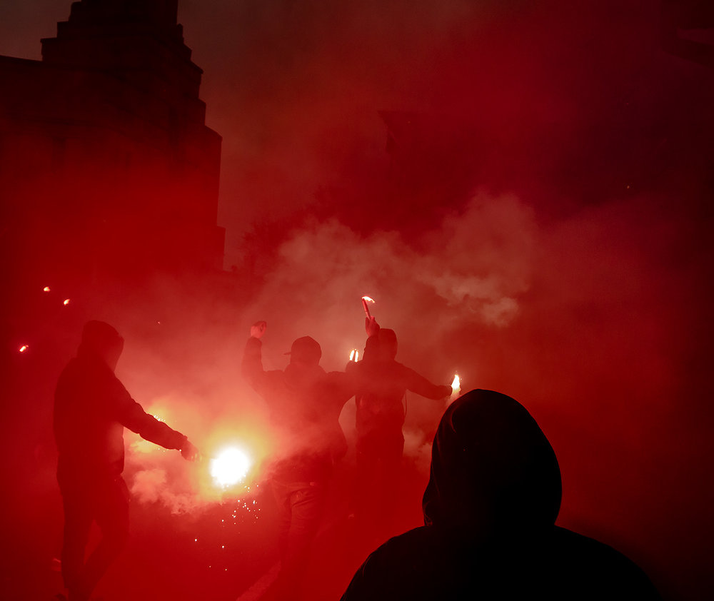 Toronto FC fans from various supporters' groups march to BMO Field in 2017 amidst red smoke and flares. Red Patch Boys, U Sector, Kings in the North, Inebriatti, Original 109 and Tribal Rhythm got together to organize this march. Image by Dennis Marciniak of denMAR Media.