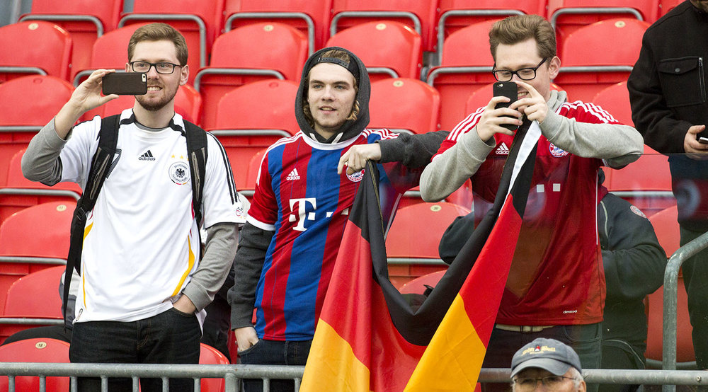 Young Bastian Schweinsteiger fans wearing the German National Team and Bayern Munich jerseys watch on as he trains. Image by Dennis Marciniak of denMAR Media.