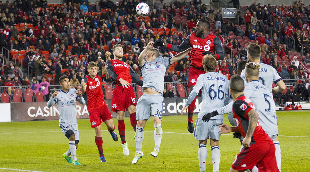 Toronto FC and Chicago Fire players try to get a head on the ball during a 2017 MLS match. Image by Dennis Marciniak of denMAR Media.