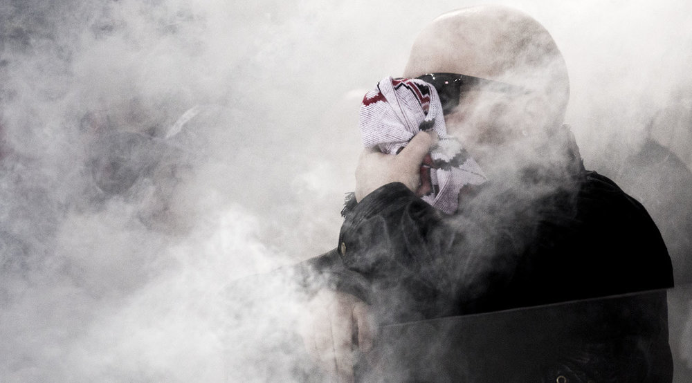 A south end supporter at BMO Field covers up in the smoky celebrations. Image by Dennis Marciniak of denMAR Media.