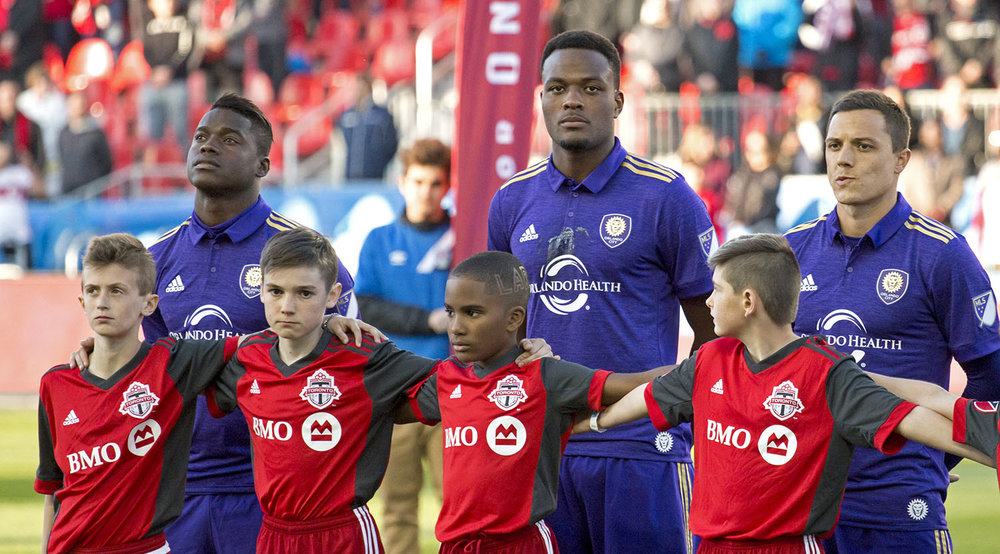Brampton native and Canadian Internation Men's Player Cyle Larin listens to the Canadian National Anthem at BMO Field before a MLS match in 2017. Image by Dennis Marciniak of denMAR Media.