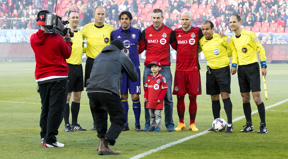Ricardo Kaká and Michael Bradley pose with a child for a picture after the coin flip that would see Toronto FC shooting in towards the south end for the first half of the match. Image by Dennis Marciniak of denMAR Photography.