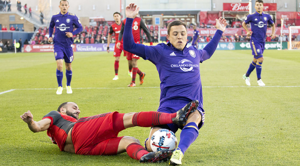 Víctor Vázquez goes for a beautiful slide tackle on a Orlando City SC player in the first half of play at BMO Field. Image by Dennis Marciniak of denMAR Photography.