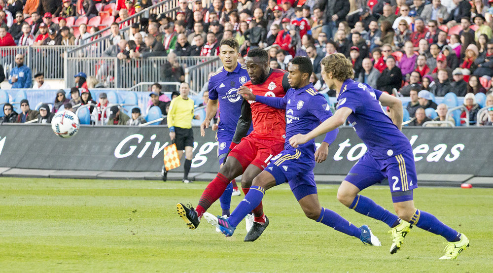 Jozy Altidore marked by three Orlando City SC defenders as they go for goal in the south end of BMO Field during a regular season match in 2017. Image by Dennis Marciniak of denMAR Photography.