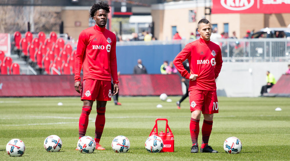 Tosaint Ricketts and Sebastian Giovinco wait to take shots on net during warm ups before a Major League Soccer match at BMO Field in 2017. Image by Dennis Marciniak of denMAR Media.