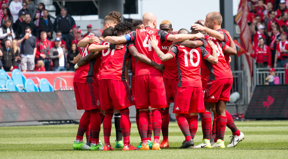 Toronto FC's starting XI against Minnesota United in a huddle before a Major League Soccer match. Image by Dennis Marciniak of denMAR Media.