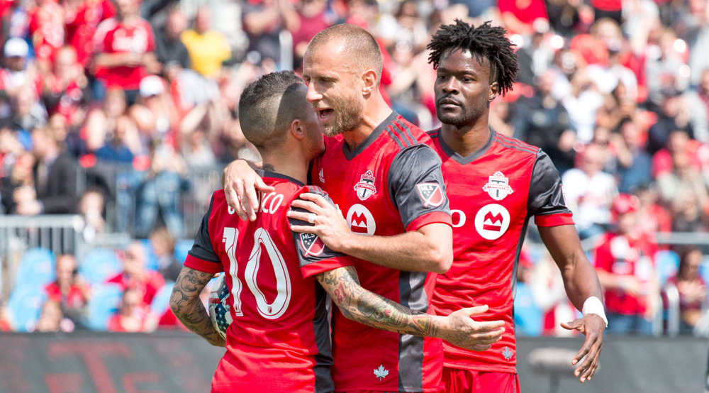 Benoît Cheyrou hugs Sebastian Giovinco after he converts the penalty kick to take Toronto FC to 1-0 in the first half. Image by Dennis Marciniak of denMAR Media.