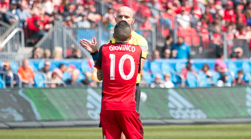 Sebastian Giovinco exchanging words with first official Allan Chapman over a call in the box. Image by Dennis Marciniak of denMAR Media.