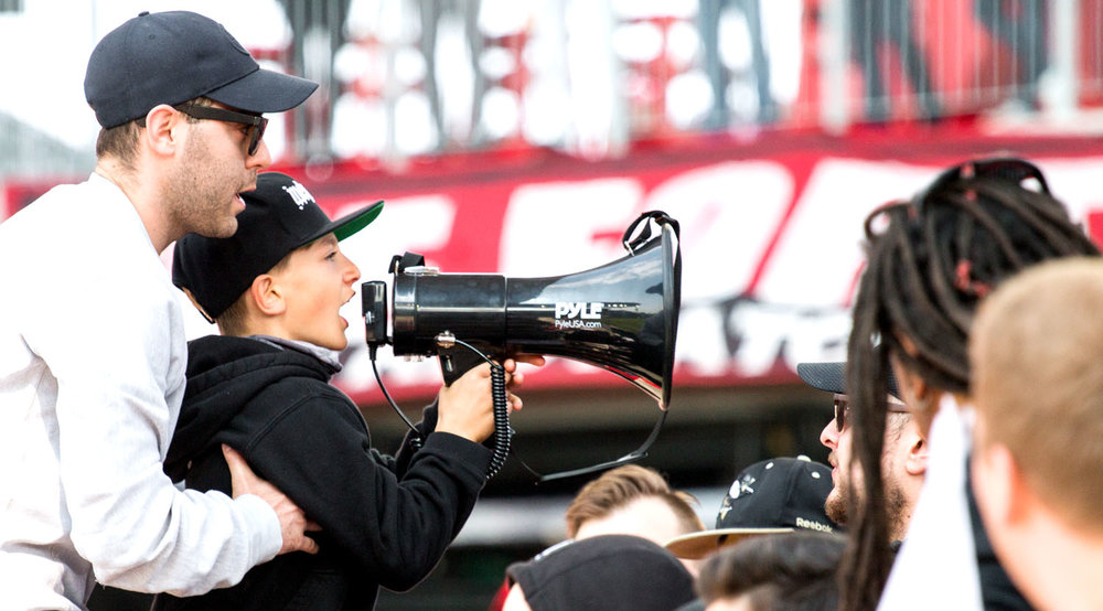 A young capo leads a section in the South End Supporters section in a chant. Image by Dennis Marciniak of denMAR Media.