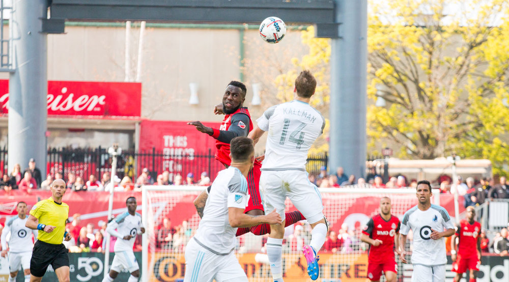 Jozy Altidore and Brent Kallmam go into the air for a header. Image by Dennis Marciniak of denMAR Media.