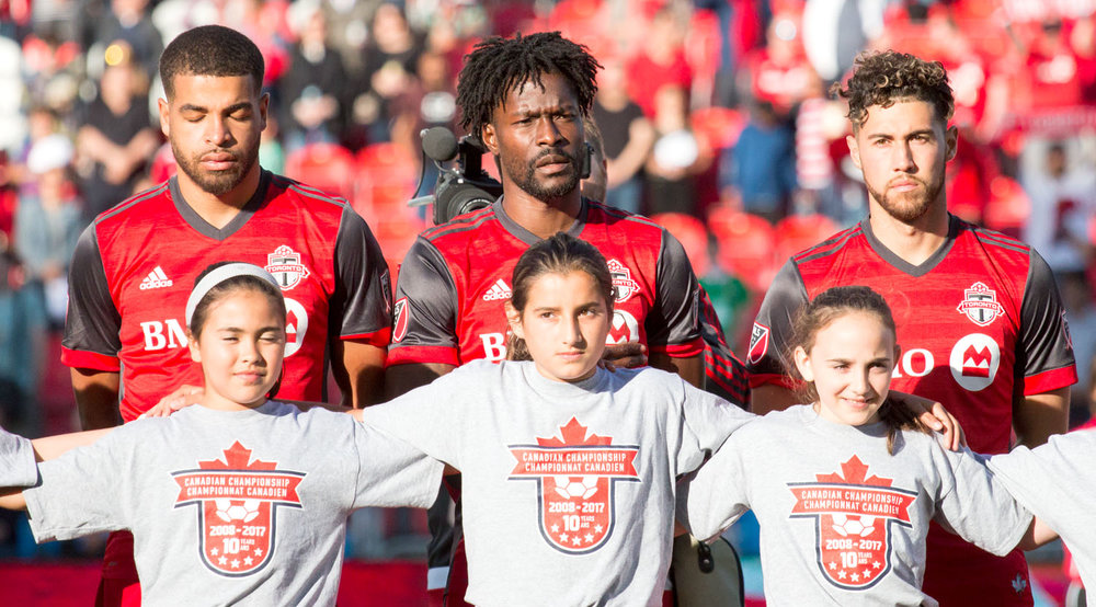 Jordan Hamilton, Tosaint Ricketts, and Jonathan Osorio line up for the Canadian National Anthem during a Canadian Championship game in 2017. Jonathan Osorio. Image by Dennis Marciniak of denMAR Media.