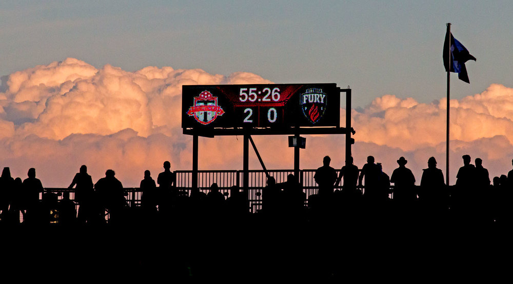 Fans look on during the 56th minute as a the sunset lights up some low lying clouds at the top of BMO Field. Image by Dennis Marciniak of denMAR Media.