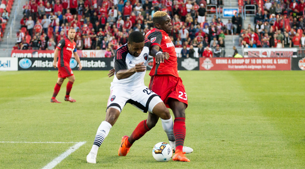 Chris Mavinga attempting to keep position of the ball against a Ottawa Fury defender during a game at BMO Field for the Canadian Championship in 2017. Image by Dennis Marciniak of denMAR Media.