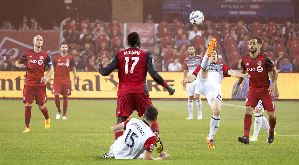Toronto FC looks on as a DC United player tries to get the ball back into the the opposing half of the field. Image by Dennis Marciniak of denMAR Media.