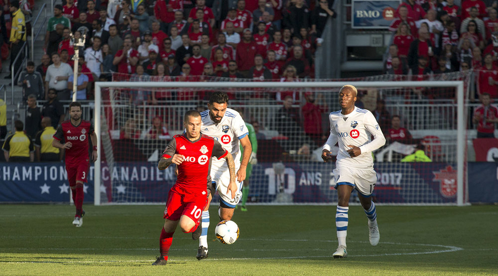 Sebastian Giovinco flies past the Montreal Impact defenders during a game in 2017. Image by Dennis Marciniak of denMAR Media.