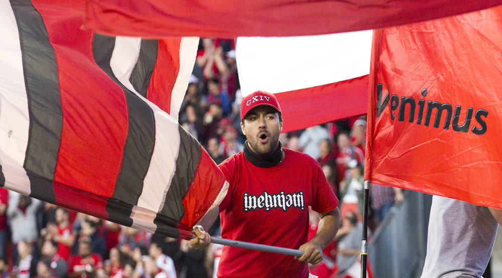 An inebriatti supporter waving a flag among other flags during the Canadian Championship Finale in 2017. Image by Dennis Marciniak of denMAR Media.
