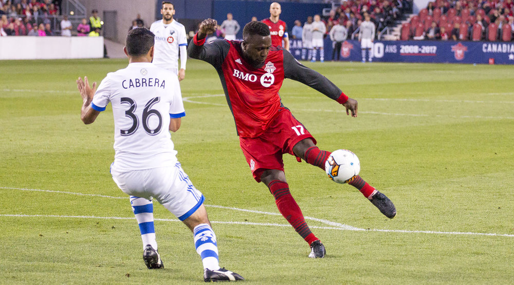 Jozy Altidore tries to take a shot on net against Montreal Impact's Cabrera who would end up blocking the ball from reaching any further. Image by Dennis Marciniak of denMAR Media.
