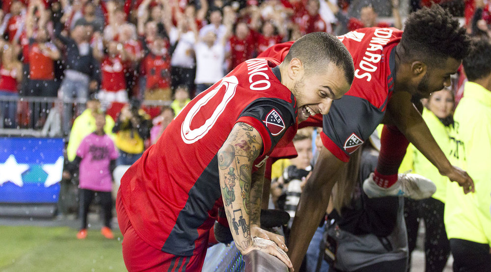 Raheem Edwards and Sebastian Giovinco jump the boards to celebrate with fans after scoring a second goal to win the match late into injury time to take the Canadian Championship! Image by Dennis Marciniak of denMAR Media.