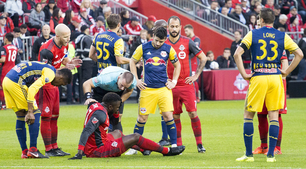 Jozy Altidore goes down to ground as the first official Chris Penso checks on him. Image by Dennis Marciniak of denMAR Media.