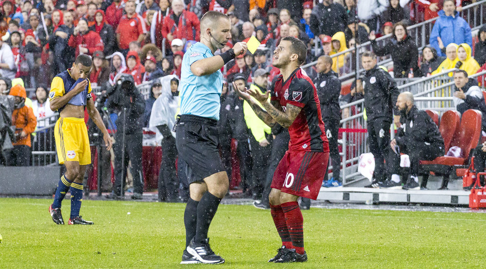 Chris Penso gives Sebastian Giovinco a yellow card in the pouring rain as the match gets out of control. Image by Dennis Marciniak of denMAR Media.