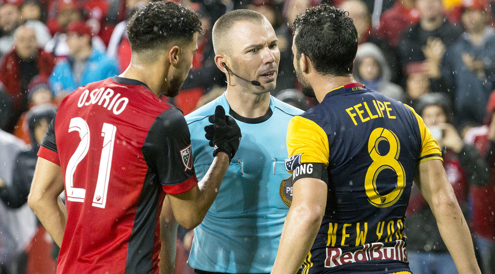 A Toronto FC and New York Red Bull player argue with the first official Chris Penso as he explains a call to both players. Image by Dennis Marciniak of denMAR Media.