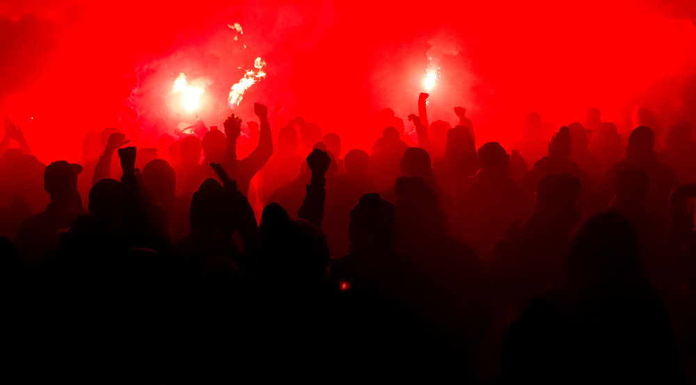 TFC supporters lighting flares and smoke in front of BMO Field during that march to the match ahead of the Major League Soccer Eastern Conference Final. Image by Dennis Marciniak of denMAR Media.