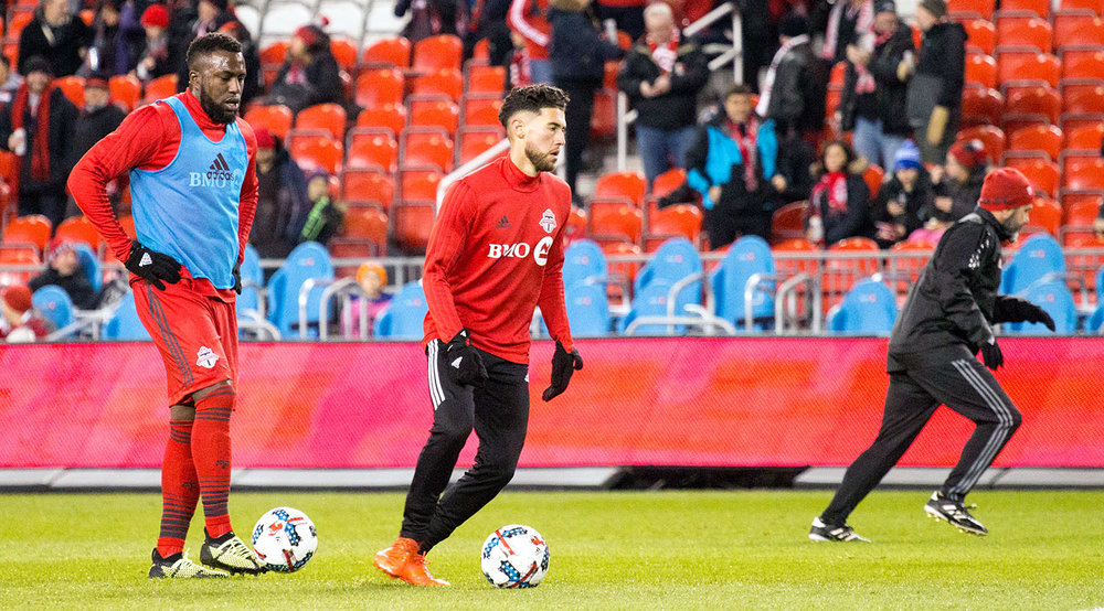 Jozy Altidore and Jonathan Osorio taking practice shots before a MLS playoff match in 2017 at BMO Field.  Image by Dennis Marciniak of denMAR Media.