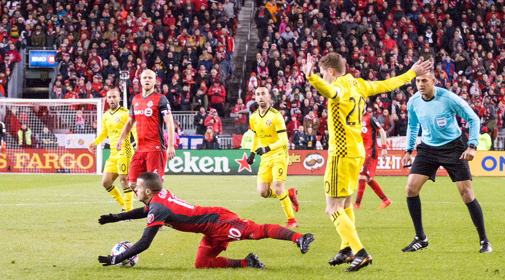 Sebastian Giovinco is taken down to ground as Ismail Elfath looks on.  Image by Dennis Marciniak of denMAR Media.