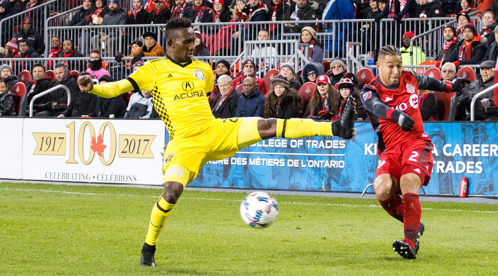 Justin Morrow avoids getting studs penetrating his skin as a Columbus Crew player makes a dangerous attack on the ball.  Image by Dennis Marciniak of denMAR Media.