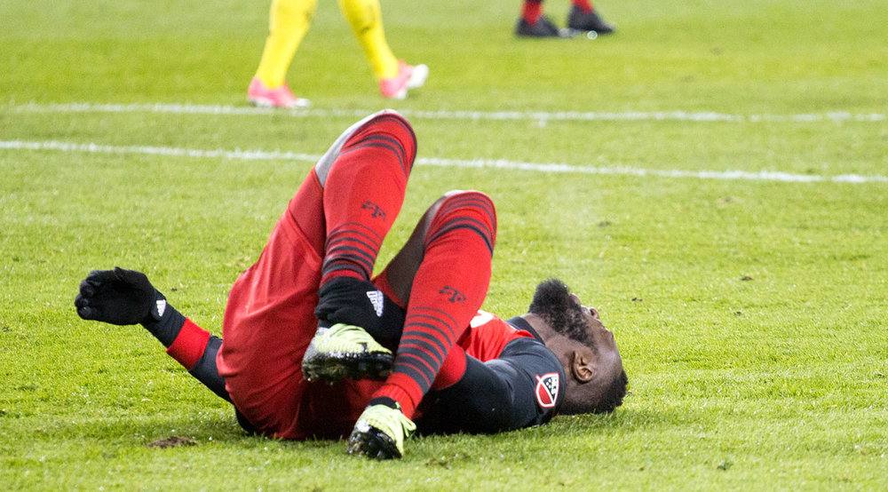 Jozy Altidore in pain on the ground due to an ankle injury. He would stay on to score the series deciding goal.  Image by Dennis Marciniak of denMAR Media.