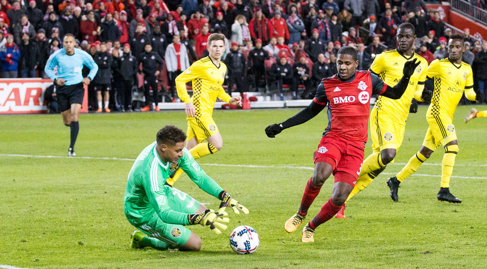 Armando Cooper trying to get to the ball before the Columbus Crew goalkeeper can get to it.  Image by Dennis Marciniak of denMAR Media.