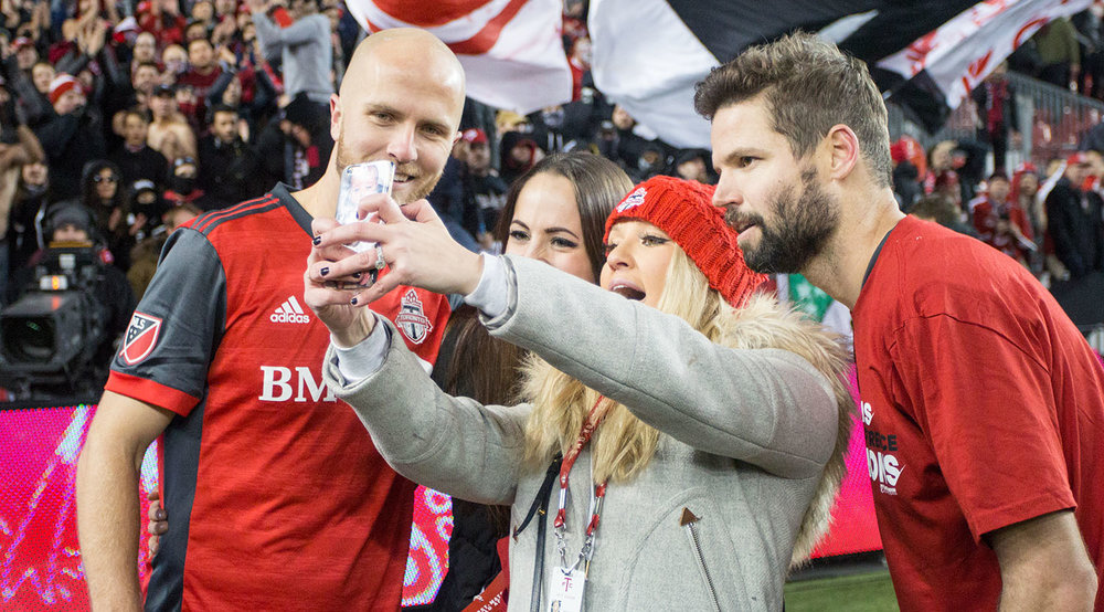 Michael Bradley and Drew Moor celebrating the Eastern Conference Final win with loved ones on the pitch at BMO Field in Toronto, Canada.