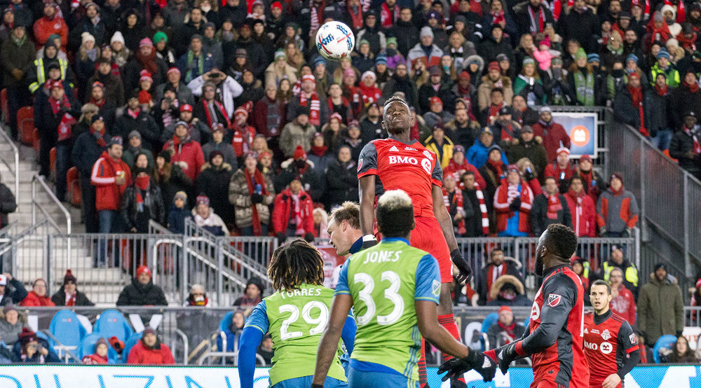 Chris Mavinga goes into the air in the Seattle 18 yard box against the Seattle Sounders during the 2017 MLS Cup Final at BMO FIeld. Image by Dennis Marciniak of denMAR Media.