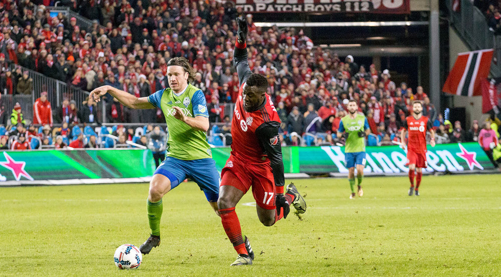 Jozy Altidore looks to take a shot on goal while a Seattle Sounders defender attempts to put a stop to that. Image by Dennis Marciniak of denMAR Media.