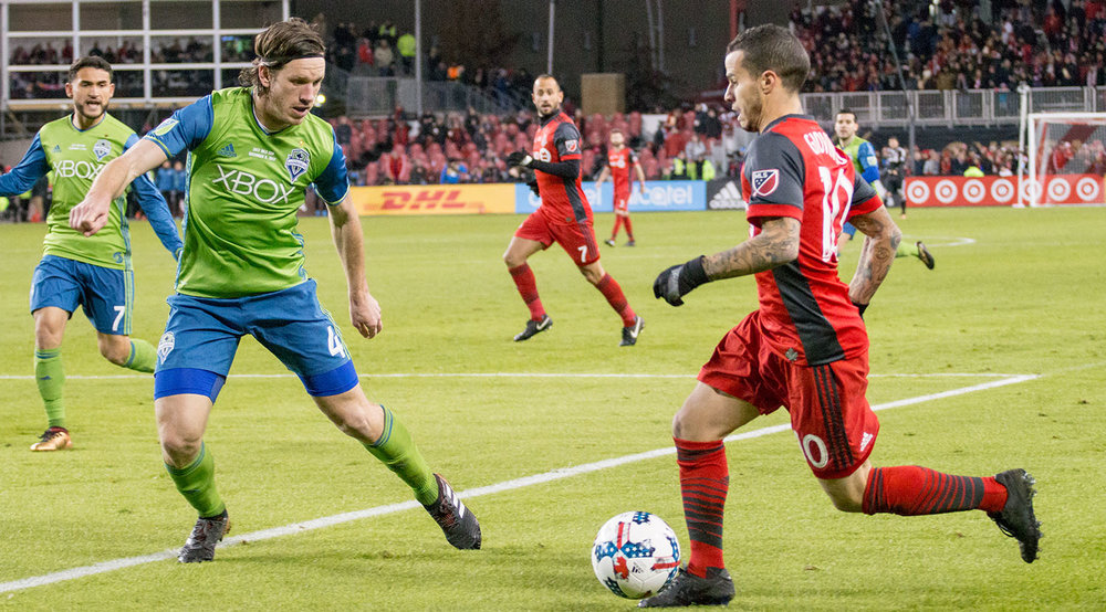 Sebastian Giovinco trying to get around a Seattle Sounder defender at BMO FIeld. Image by Dennis Marciniak of denMAR Media.