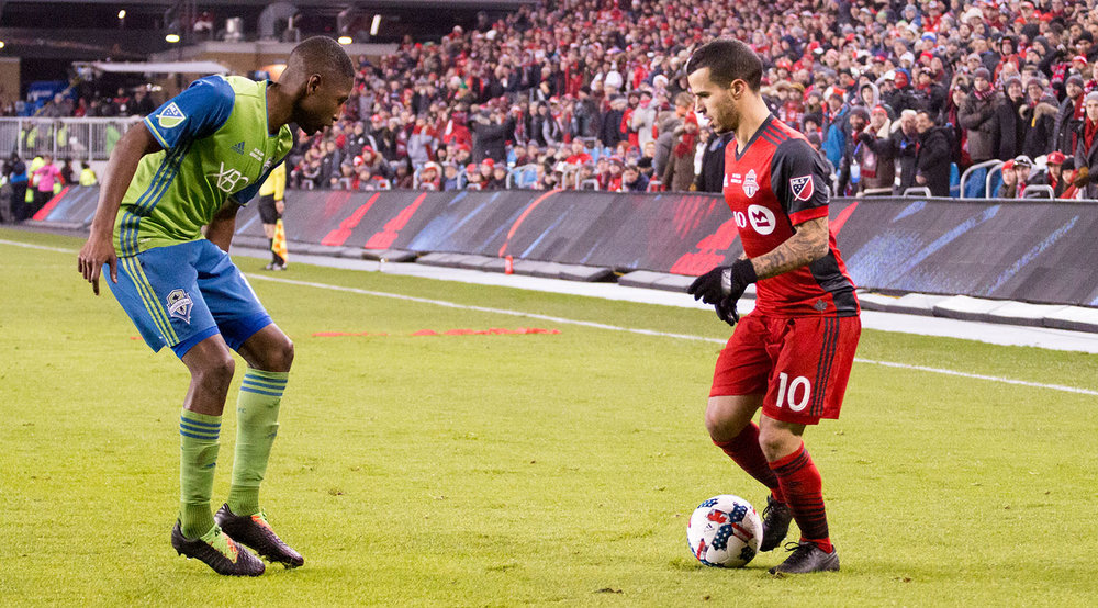 Sebastian Giovinco tries to get past another Seattle Sounder defender at BMO FIeld in 2017. Image by Dennis Marciniak of denMAR Media.