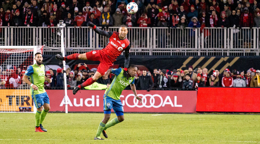 Justin Morrow takes flight during the 2017 MLS Cup Final to get a header to the ball at BMO FIeld. Image by Dennis Marciniak of denMAR Media.