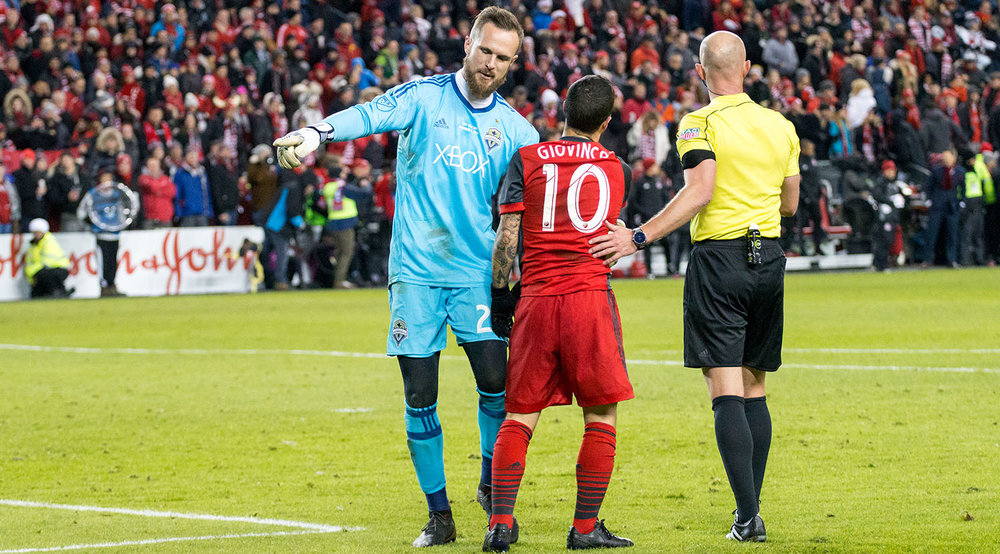 Stefan Frei now tries to convince Sebastian Giovinco to take it to the end line in hopes of playing with 10 men for a few minutes. Image by Dennis Marciniak of denMAR Media.