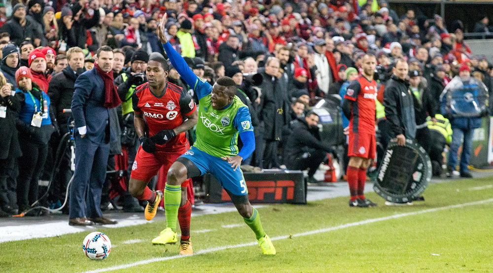 Greg Vanney looks on as Toronto FC and Seattle Sounders players battle for the ball near the coaching area. Image by Dennis Marciniak of denMAR Media.