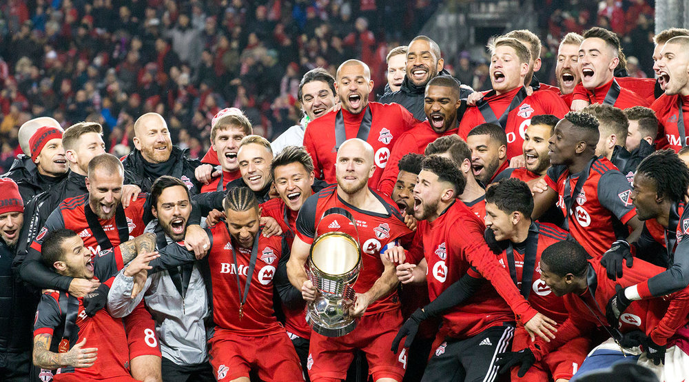 Michael Bradley about to lift the 2017 MLS Cup trophy at BMO Field after winning 2-0. Image by Dennis Marciniak of denMAR Media.
